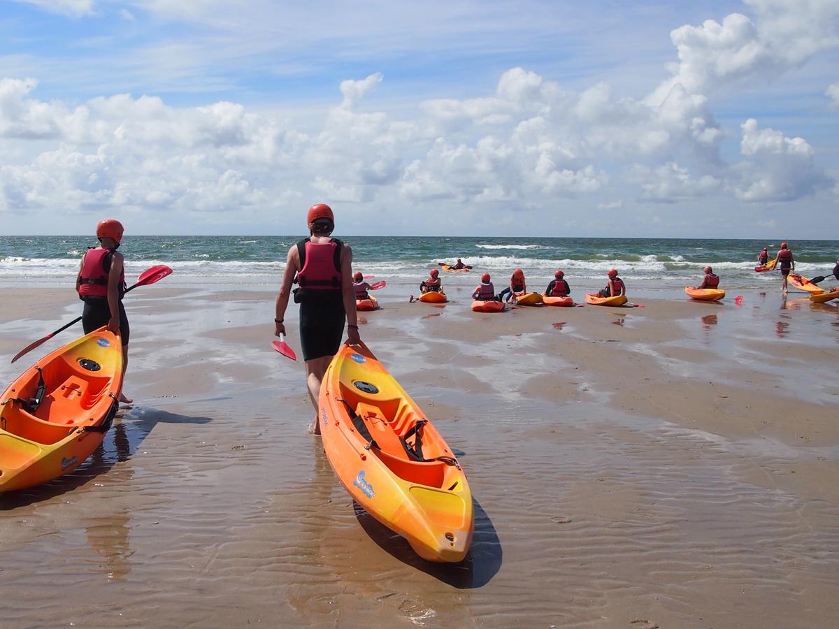 Branding kajakken en surfen op de golven van de Noord-Zee in Camperduin.