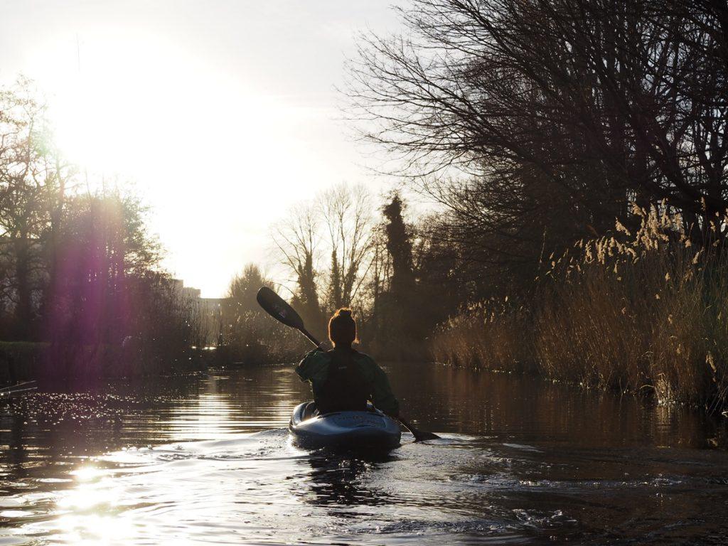 Een prachtige foto van een laag hangende zon met een kajakker op het water in de Bergermeer.