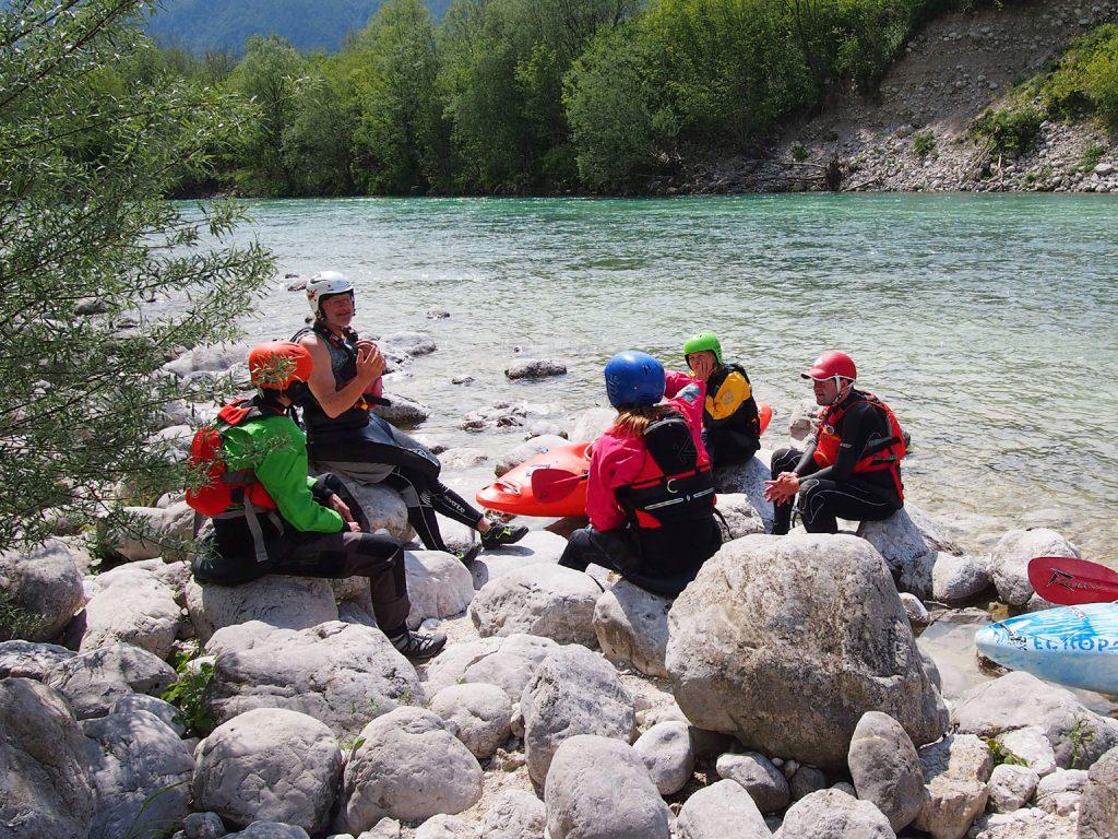 Kajakkers krijgen uitleg aan de waterkant tijdens een weekje wildwaterkajakken in de meivakantie.